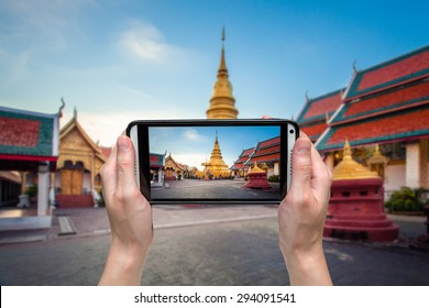 hand woman taking photo at wat phratad haripunchai in lamphun, thailand.