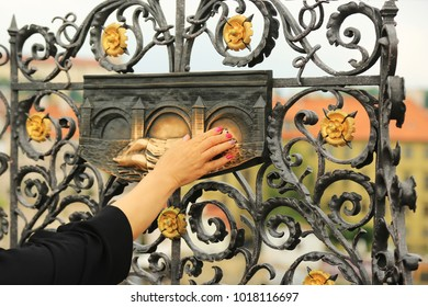 The hand of a woman touches the relief of St. John on the Charles Bridge in Prague