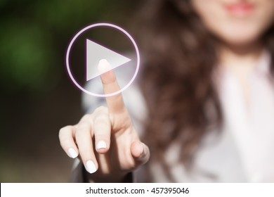 Hand of a woman touching play button on digital display. Person starting new project and pressing interactive button on touch screen.