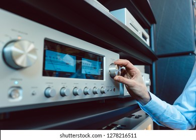 Hand of woman turning up volume of Hi-Fi amplifier in her home