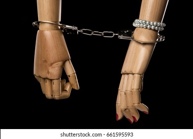 Hand of  woman tying hand of man with handcuffs. Bondage or marriage. Isolated on black background. With copy space text. Studio Shot.