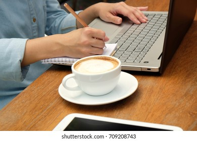 Hand of woman typing on laptop keyboard and writing on paper note, using computer with hand typing on keyboard