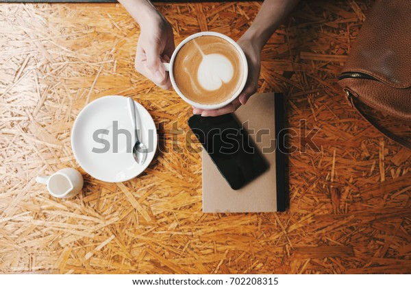 Hand of woman use smart phone while drinking coffee on wooden background.