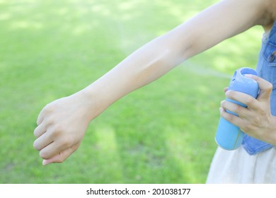 Hand of the woman using the insect repellent