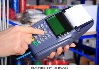 Hand of woman using payment terminal in an electrical shop, paying with credit card, credit card reader, finance concept