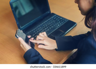 hand woman using smart phone and working notebook computer