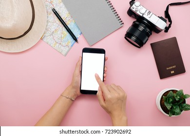 Hand of woman using smart phone for planing vacation trip with map camera and notebook.