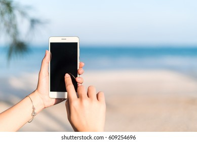 Hand of woman using smartphone mobile, blur the background of the beach.