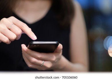Hand of woman using smartphone on wooden table,Space for text or design.