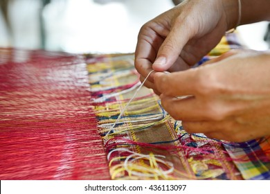 Hand of a woman weaving traditional silk fabric in Thailand