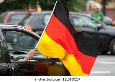 hand of a woman who holds a German flag through a car window and waves it