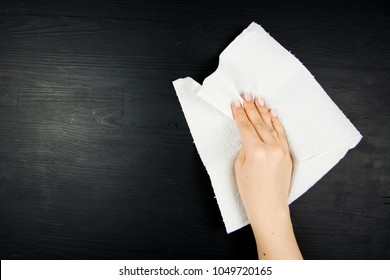 Hand of woman wiping black wooden background with paper towel