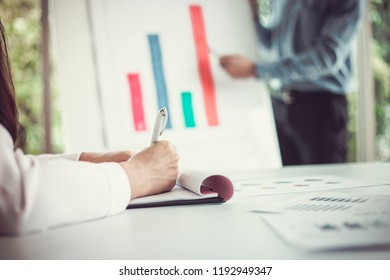 Hand of woman working with document front businessman giving a presentation to his employees in the meeting room.