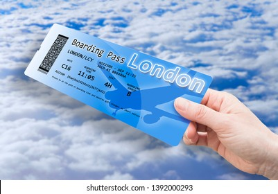 Hand of a women holding an airplane ticket to London - The contents of the image are totally invented and does not contain under copyright parts. The QR code is invented and does not contain any data