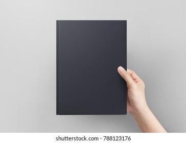 Hånd kvinner holder svart bok cover blank topp utsikt. Blankt bokomslag.