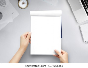 Hand women holding blank book A4 size on office table top view.
