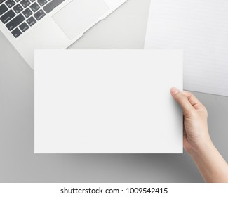Hand women holding blank paper A4 size on office table top view.