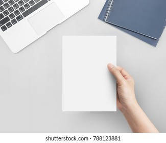 Hand women holding blank paper A5 size on office table top view.