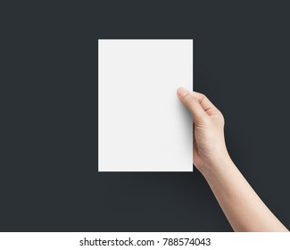 Hand women holding blank paper A5 size on top view at black background.