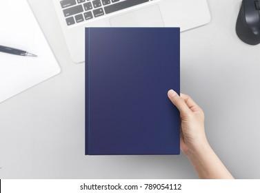 Hånd kvinner holder bokomslag blank på kontoret tabellen topp utsikt. Blankt bokomslag.