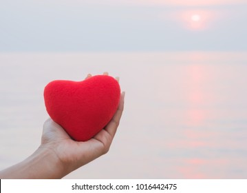 Hand of women holding red heart on the beach in sunset