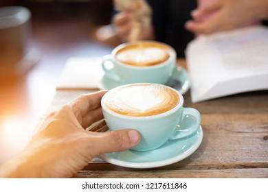 Hand Frauen und Mann legte ein Latte-Art Kaffee Kaffee heißen Kaffee auf hölzernem Tisch.barista Liebe Kunst Konzept.