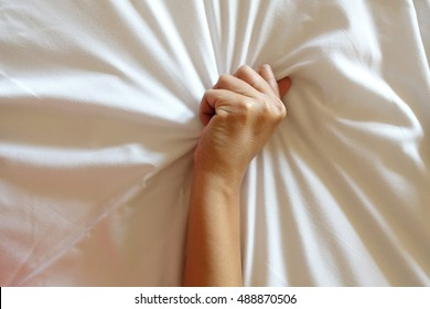 hand of women pulling white sheets in ecstasy, orgasm.