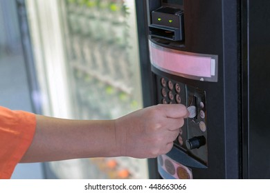 Hand of women put a coin into water drink vending machine