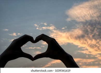 Hand of women showing heart shape with clouds and sky in background.