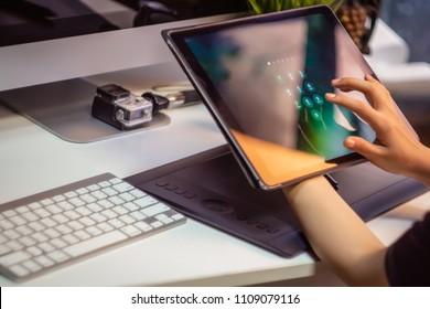 Hand of women tying tablet computer with password login on screen, selective focus