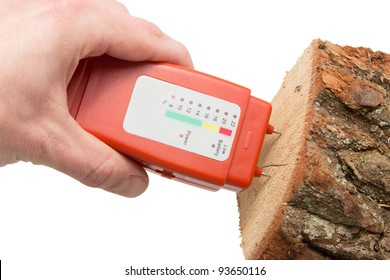 Hand with a wood moisture meter and firewood over a white background