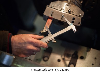 Hand worker with caliper in low light environment makes measurement. Photograph aperture with defokus of background