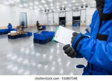 Hand of worker with clipboard checking ready meals goods in the warehouse., Import and export management system for customer service concept.