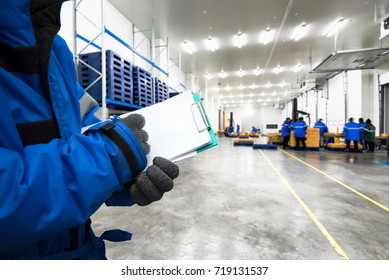 Hand of worker with clipboard checking ready meals goods in the warehouse., Import and export loading management for customer service concept.