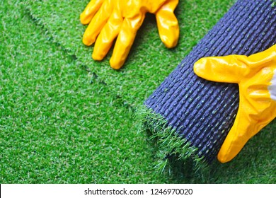 Hand of a worker in gloves with a artificial lawn grass. Artificial turf laying process.