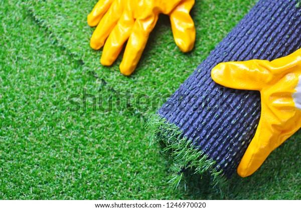 Hand eines Arbeitnehmers in Handschuhen mit künstlichem Rasengras. künstliches Verlegen von Rüben.