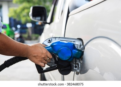hand worker hold fuel nozzle during refill fuel at gas station.