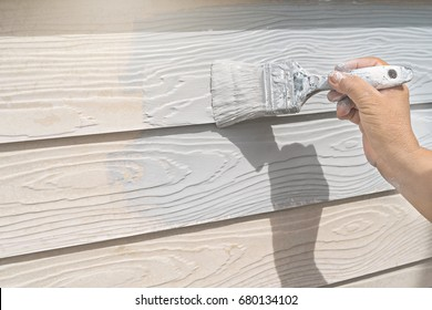 Hand of worker painting on wood wall new house at construction site.