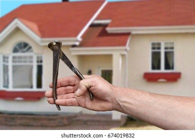 Hand of worker with pincers. Cottage repair