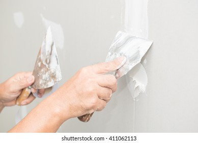 Hand of worker with plaster and trowel to gypsum board