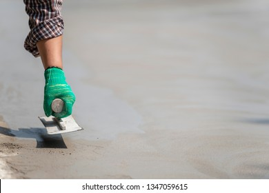 Hand worker with trowel smoothing a wet concrete