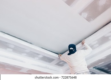 hand of worker using gypsum plaster ceiling joints at construction site