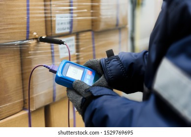 Hand of worker using thermometer to temperature measurement in the goods boxes with ready meals after import in the cold room or warehouse for keep temperature room - Shutterstock ID 1529769695