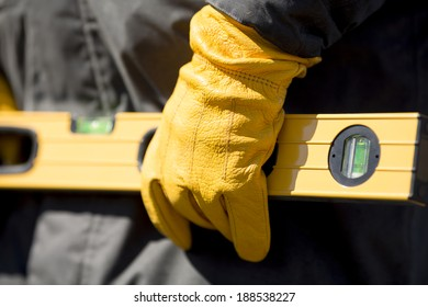 hand of worker with yellow glove and level