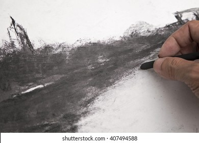 A hand working on charcoal drawing