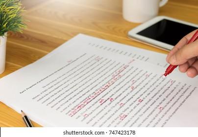 Hand, die auf Papier zum Korrekturlesen arbeitet