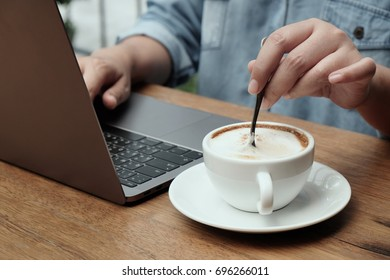 Hand working for two laptop with coffee  on wooden background, typing laptop with coffee on table