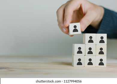 Hand working woman putting wood cube block on top pyramid,Human resources, social networking, assessment center concept, personal audit or CRM concept - recruiter complete