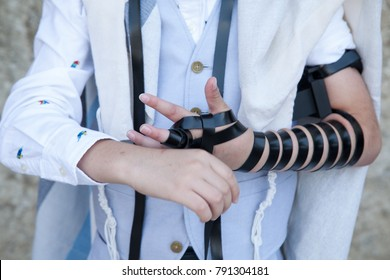 Hand wrap tefilin around the other hand with the Kotel in background. Jewish teenager 13 years old  celebrates bar mitzvah at the wailing wall and praying with hands on the stones
