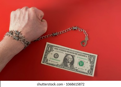 Hand wrapped with barbed wire with hook and one dollar on red background